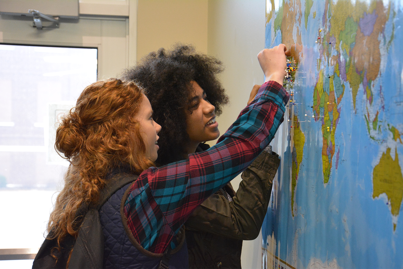 students sticking pins in map