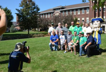 Alumni posing for a picture in front of Penn Hall
